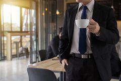 Business man holding coffee cup and looking away while standing outdoors with coffee shop. In the background, Rebooting after hard working day Stock Photo