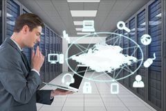 Business man holding a computer and graphics in server room. Digital composite of Business man holding a computer and graphics in server room Stock Image