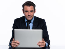 Business man holding computer looking at camera Royalty Free Stock Images