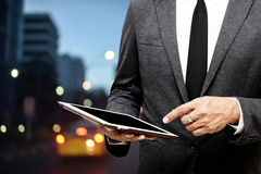 Business man holding computer tablet selective focus on pointing. Fingers with city light background Royalty Free Stock Images