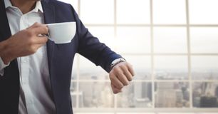 Business man holding a cup of coffee against building background Stock Image