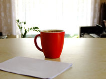 Business Man. Holding a Cup of Coffee with one Hand and having white Paper on the Table Stock Photos