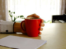 Business Man. Holding a Cup of Coffee with one Hand and having white Paper on the Table Royalty Free Stock Photo