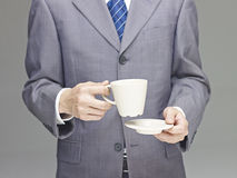 Business man holding a cup of coffee or tea Royalty Free Stock Images