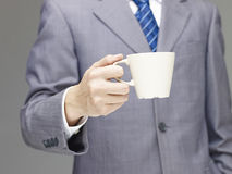 Business man holding a cup of coffee or tea Royalty Free Stock Photography