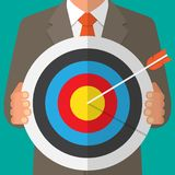Business man holding a dart board with a direct hit on target. Vector illustration Royalty Free Stock Images