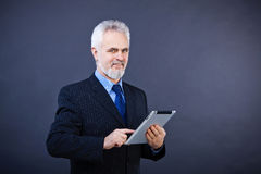 Business man holding a digital tablet. Studio shot of a smiling handsome business man holding a digital tablet Royalty Free Stock Photo