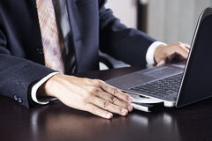 Business man holding Disk insert to laptop Stock Images