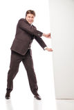 Business man holding empty board and pointing Royalty Free Stock Photo