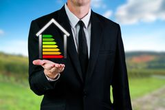 Business man holding an energetic house. Saving energy and eco environment concept. With green background royalty free stock images