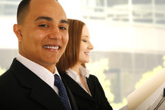 Business Man Holding Folder And Smile. Two business people holding folder. the man look to camera and smile while the woman smile and looking at her folder or stock photography