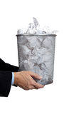 Business man holding full trash can. Business man holidng a trash can full of papers on a white background with copy space Stock Image