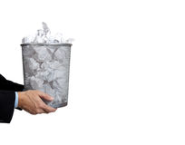 Business man holding full trash can. Business man holding a trash can full of papers on a white background with copy space Royalty Free Stock Photo