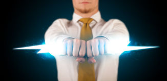 Business man holding glowing lightning bolt in his hands Stock Image