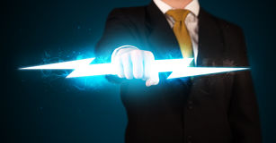 Business man holding glowing lightning bolt in his hands Royalty Free Stock Image