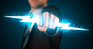 Business man holding glowing lightning bolt in his hands. Concept stock image