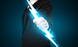 Business man holding glowing lightning bolt in his hands. Concept royalty free stock photo