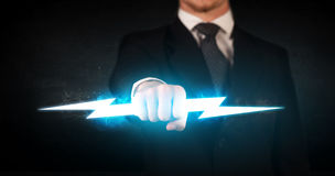 Business man holding glowing lightning bolt in his hands. Concept stock photos