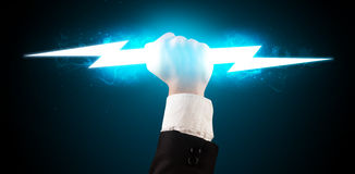 Business man holding glowing lightning bolt in his hands Stock Images