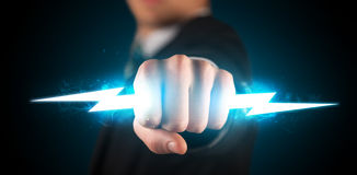 Business man holding glowing lightning bolt in his hands. Concept stock photography