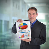 Business Man Holding Graph Chart. A business man is holding a paper with various bar and lines graphs to represent finance. There is a faded office in the Stock Image