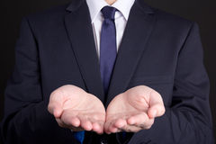 Business man holding hand presenting product. Over dark background royalty free stock photo