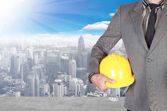 Business man holding helmet at high building construction site a Stock Image