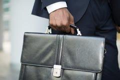 Business man holding his briefcase Stock Photos