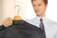 Business man holding his coat and looking at it Stock Photo
