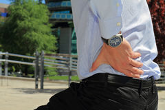Business man holding his lower back.  Pain relief concept Stock Image