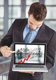 Business man holding laptop showing red arrow with black business doodles against blurry background Stock Photo