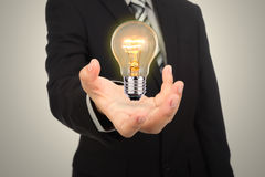 Business man holding light bulb Royalty Free Stock Image