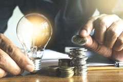 Business man holding light bulb and a coin on the desk in office for financial,accounting,energy,idea concept. stock photos
