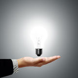 Business man holding light bulb in his hand Stock Images