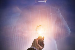 Business man holding light bulb on stock market investment trading and back of suit businessman Royalty Free Stock Photo