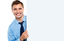 Business man holding a long blank banner ad. Smiling at camera Royalty Free Stock Photo