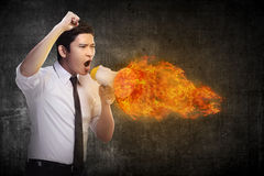 Business man holding megaphone in fire and shouting Royalty Free Stock Photo