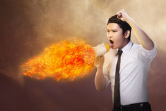 Business man holding megaphone in fire and shouting Stock Image
