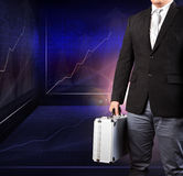 Business man holding metal strong breifcase standing against ind Royalty Free Stock Image