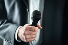Business man holding microphone. Public speaking and giving speech in suit for audience concept. royalty free stock images