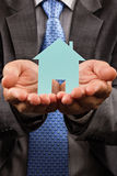 Business man holding a model of a house in his hands. Conceptual image Royalty Free Stock Photo