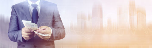 Business man holding money. Panoramic banner. Double exposure of Businessman with money in hand with cityscape blurred building background. Concept of finance Royalty Free Stock Photo