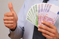 Business Man holding money and showing thumbs up. Success, investment, financial growth, profit, dividends concept Royalty Free Stock Photos