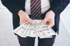 Business man holding money US dollar bills royalty free stock photos