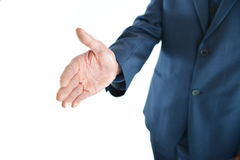 Business man holding out hand for a handshake. With focus on the hand Royalty Free Stock Photo