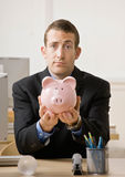 Business man holding out piggy bank Stock Photography