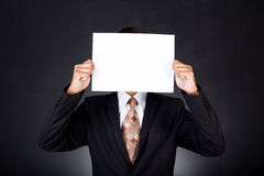 A business man holding a paper in front of his face Stock Image