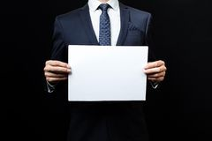 Business man holding a paper. A business man holding a paper. Studio shot Royalty Free Stock Photography