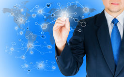 Business man holding pen while drawing network link nodes over world map background. Royalty Free Stock Photo