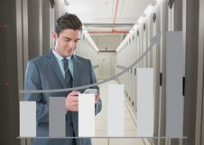 Business man holding a phone and graphics in server room. Digital composite of Business man holding a phone and graphics in server room Royalty Free Stock Photos